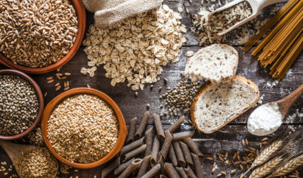Grains, seeds, bread and pasta on a wooden table