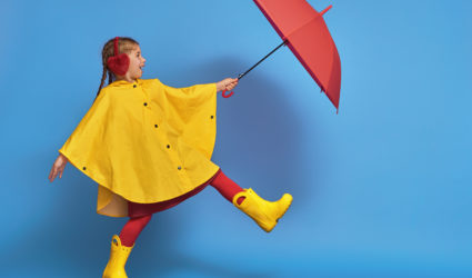 Child in Rain boots and jacket with umbrella