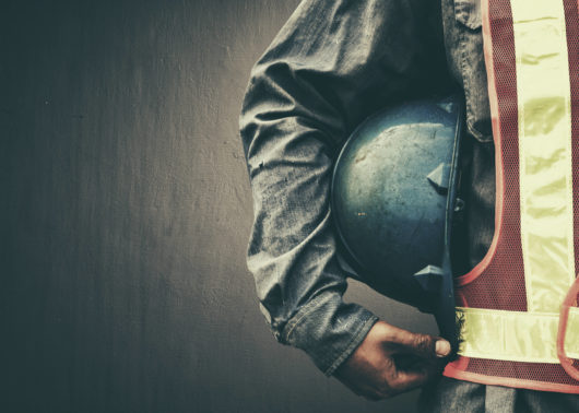 Worker in safety gear holding a construction helmet