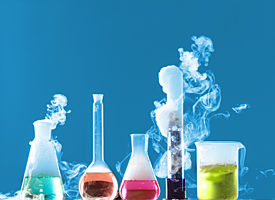 lab beakers and flasks filled with colourful liquid giving off fumes