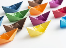 Multicolored paper boats representing new staff